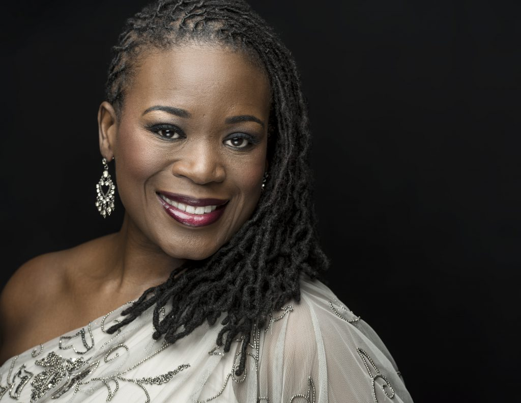 A handsome African American woman with braided hair and clothed in silver smiles at the viewer