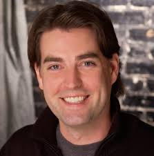 A young white man with brunette hair smiling