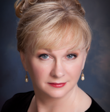 A middle-aged white woman with blue eyes, blond hair, and pearl earrings